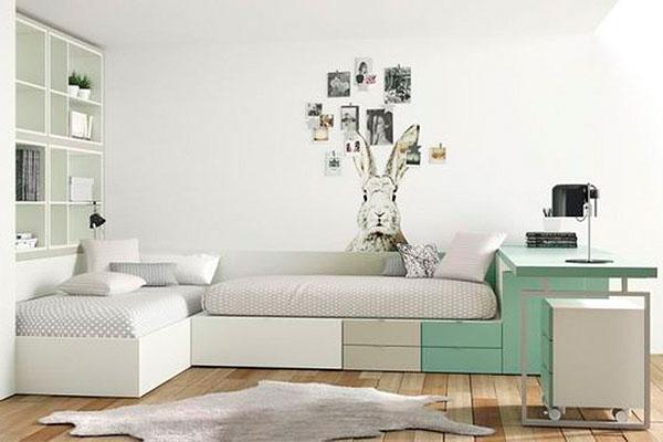 Habitació juvenil amb dos llits i taula d'escriptori de color verd menta